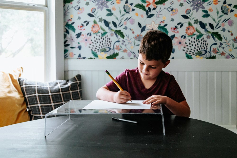 young boy drawing a picture on an acrylic lap desk