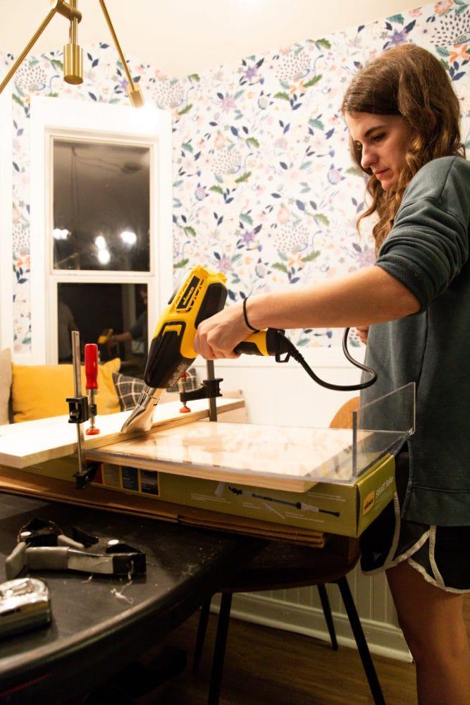 woman applying heat to plexiglass using a heat gun