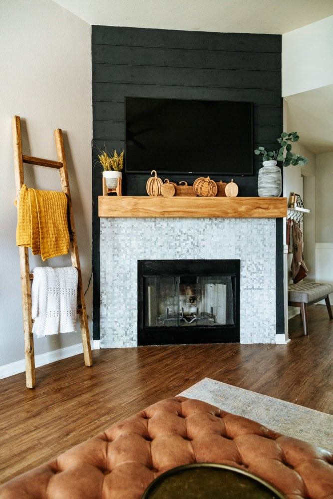 fireplace decorated for fall with wooden carved pumpkins
