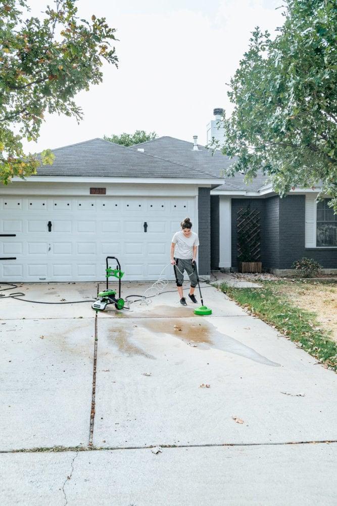 woman pressure washing a driveawy
