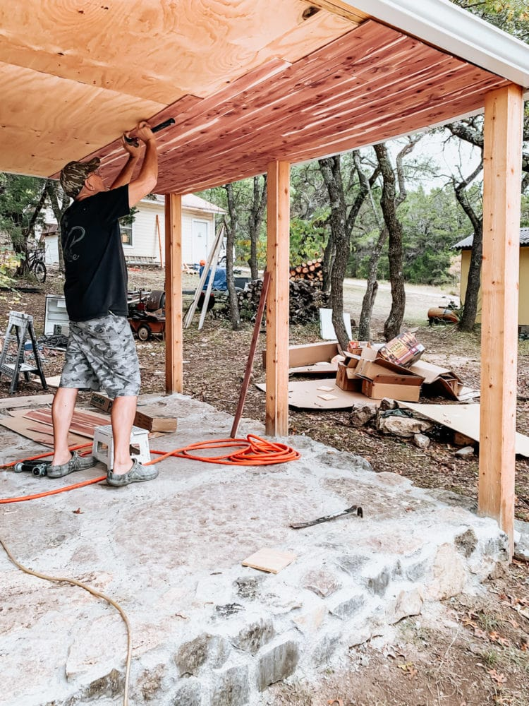 man nailing a cedar plank into the underside of an exterior pergola