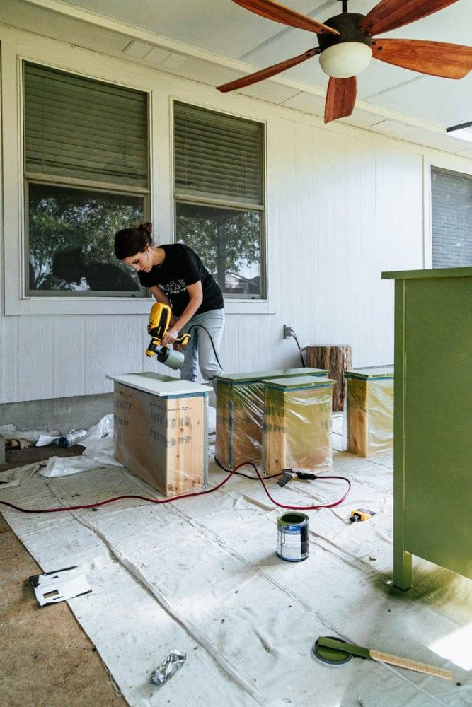 woman using a paint sprayer to paint an IKEA dresser