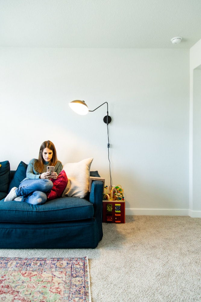 woman on a couch with a lamp overhead