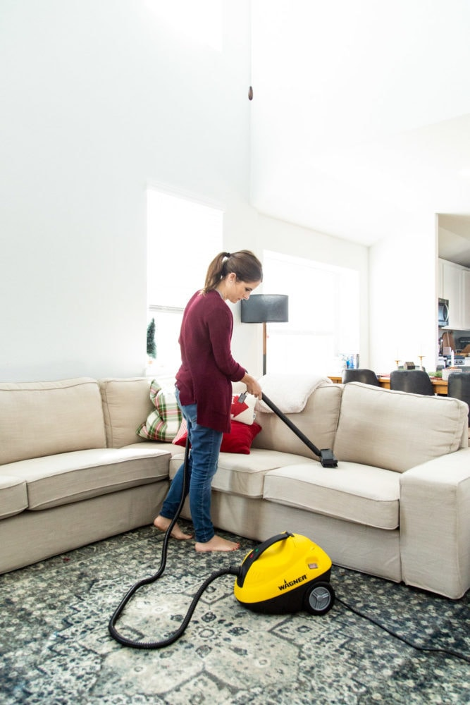 woman cleaning a sofa using a steamer