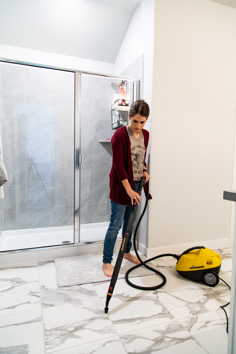 woman cleaning a bathroom floor using a steamer