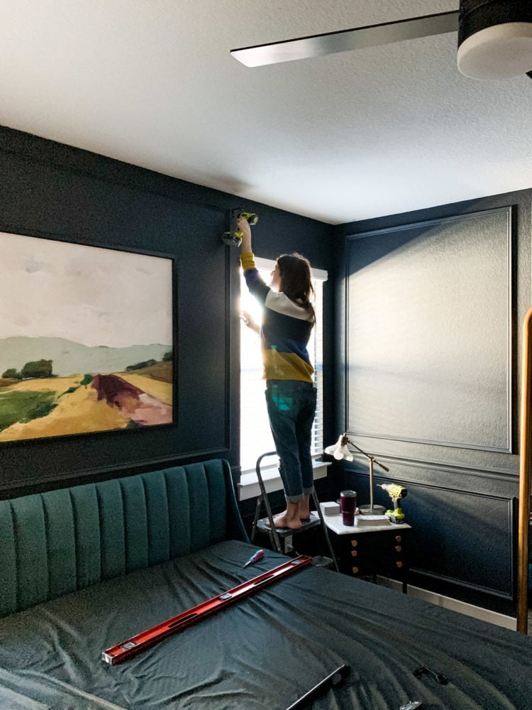 woman hanging a curtain rod
