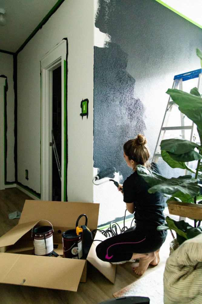 woman painting a wall dark blue