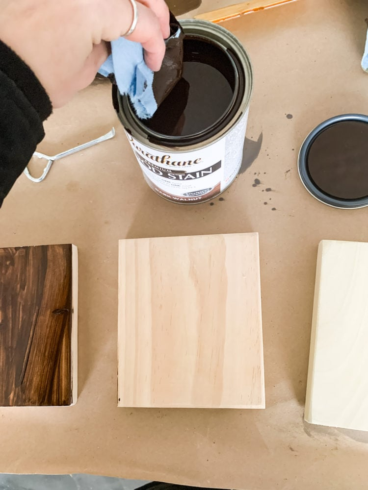 woman's hand staining a board