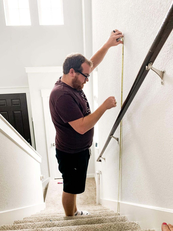 Man measuring a wall to hang photos in a staircase