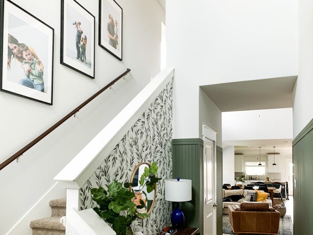 entryway with family photos going up stairs