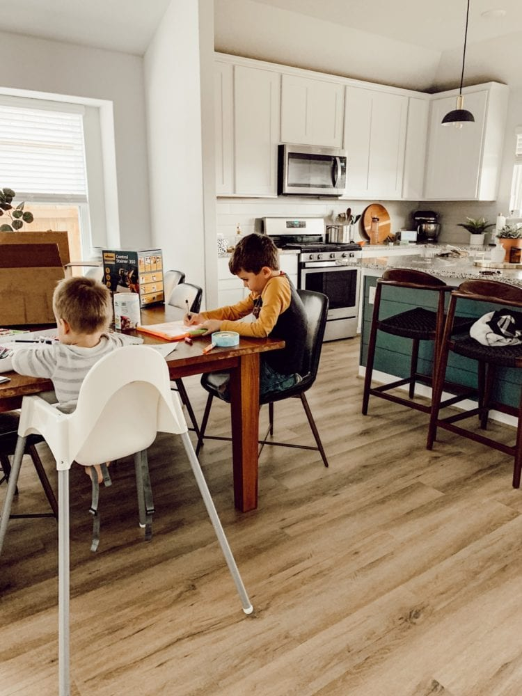 two young boys playing at a dining table