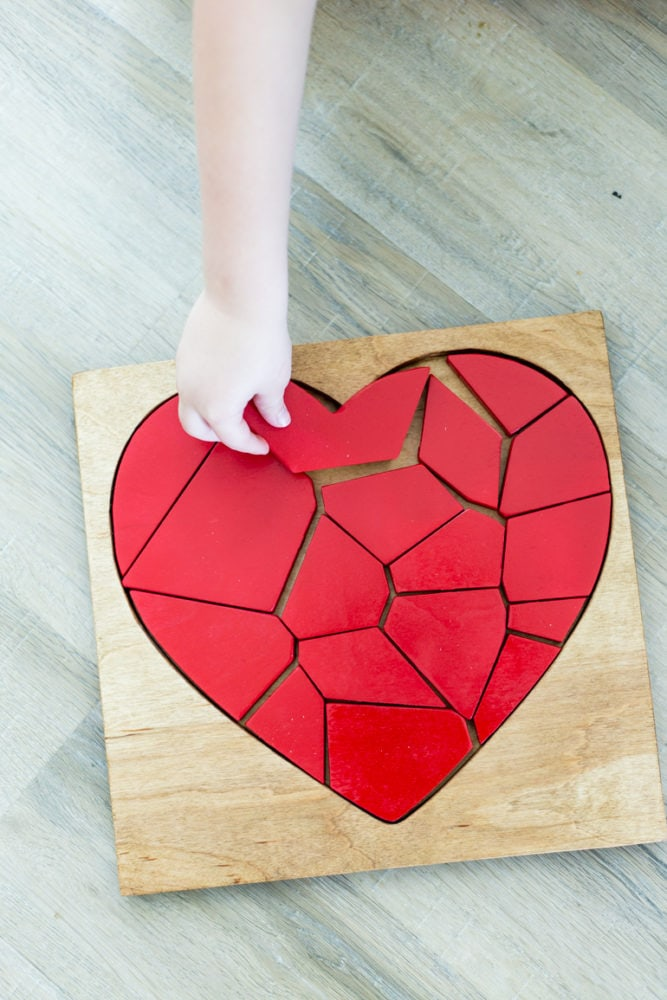 A boy's hand putting a piece into a DIY wood puzzle