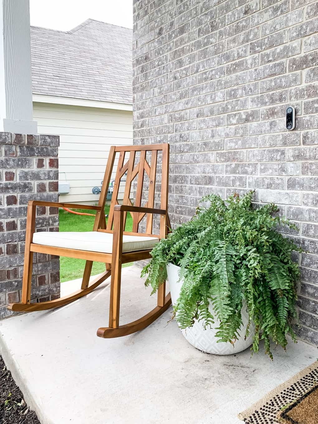 Front porch rocking chair and large fern