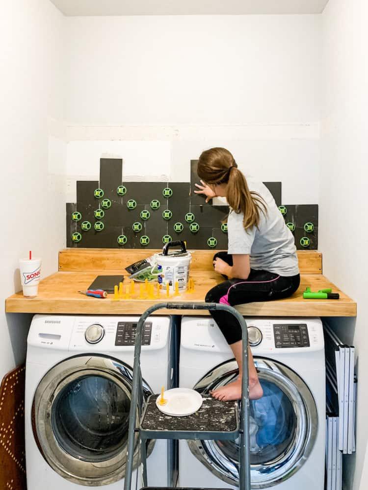 Woman installing basalt tile