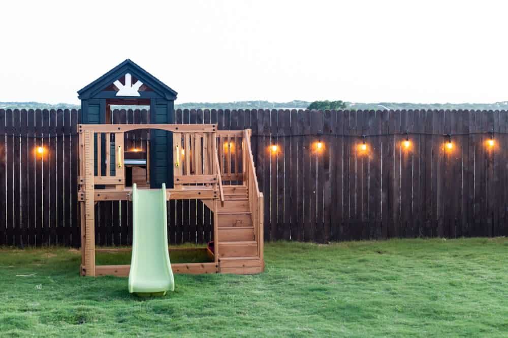 small play structure near a lighted fence