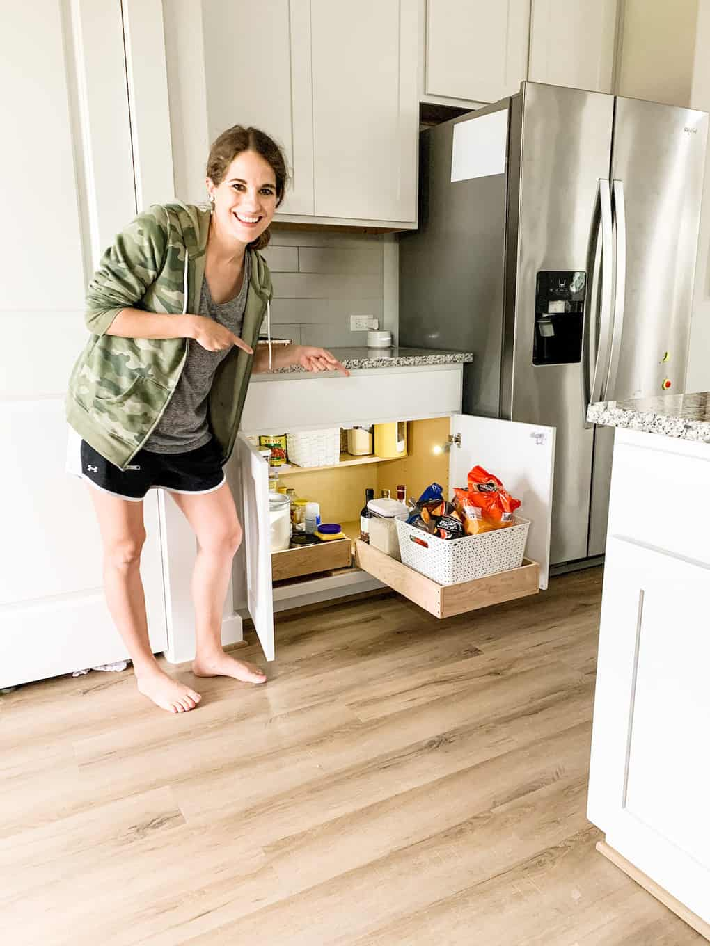 woman posing with DIY pull out cabinet drawers