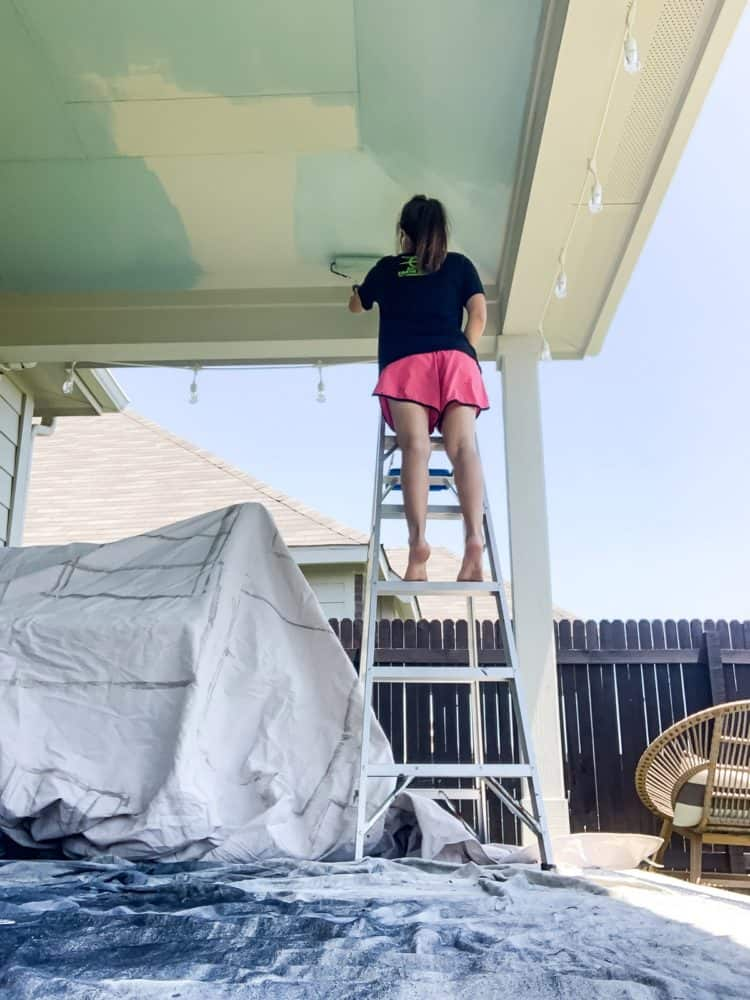 woman painting a back porch ceiling haint blue