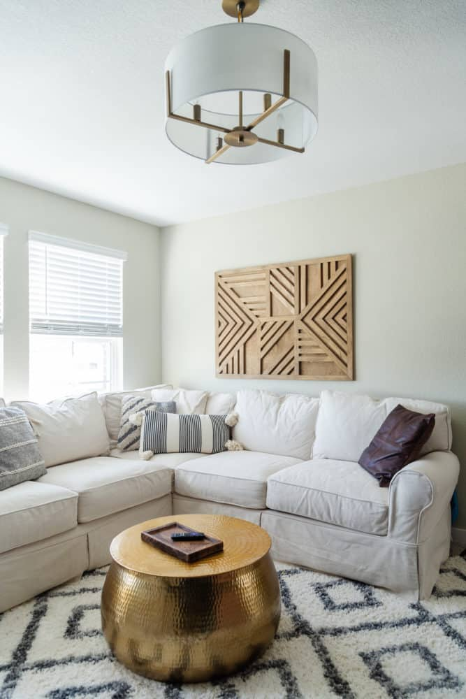 corner of a cozy family room with a sectional and a plush rug