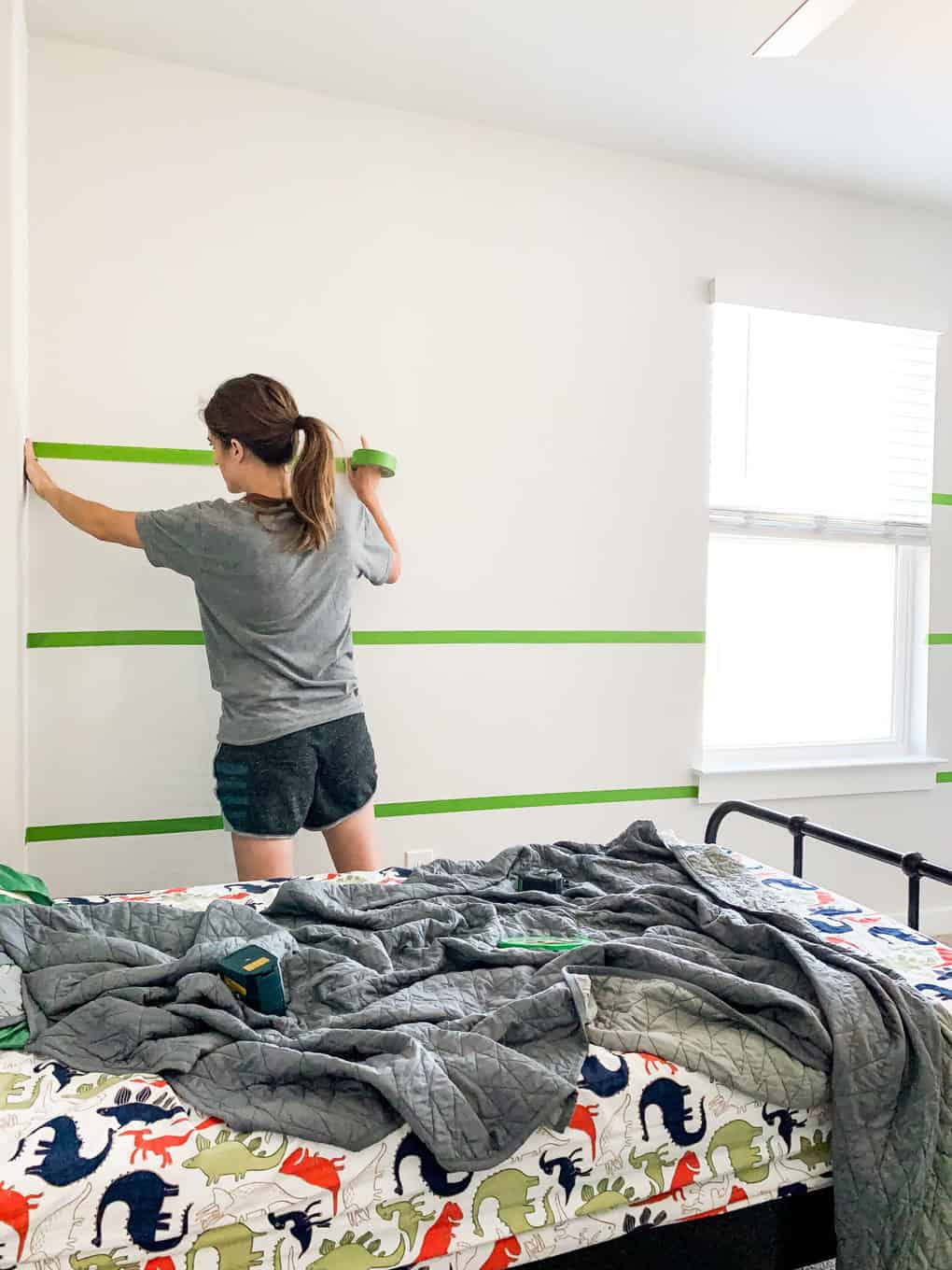 woman putting FrogTape on a wall to paint stripes