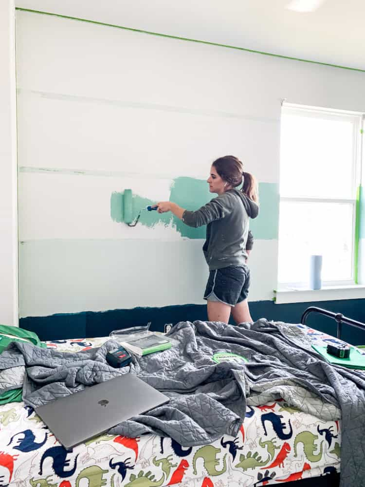 woman painting stripes on a wall