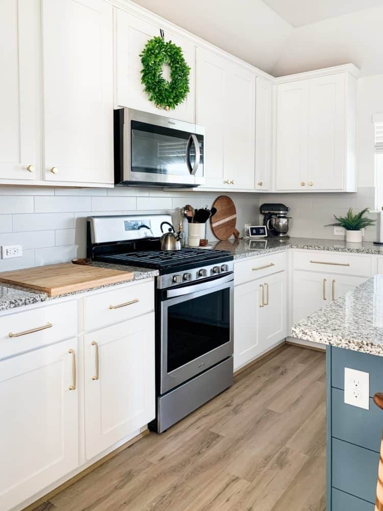A white and gray kitchen with gold cabinet pulls