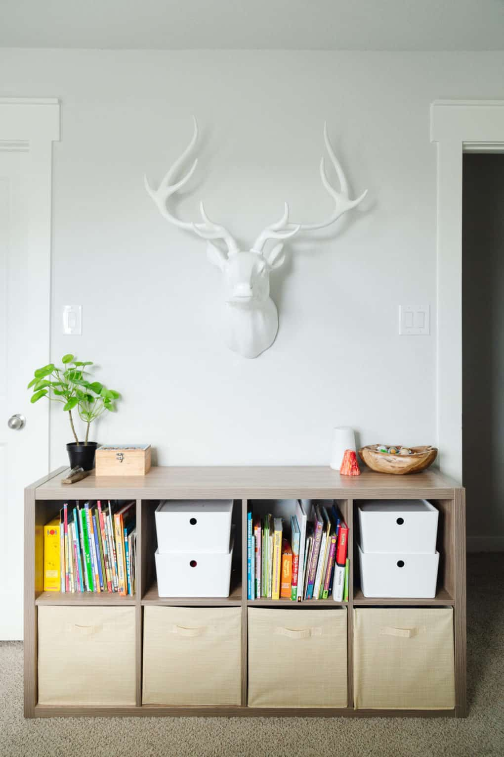 kid room with bookcase and faux deer head on the wall
