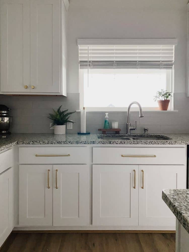 white kitchen with granite counters and gold hardware