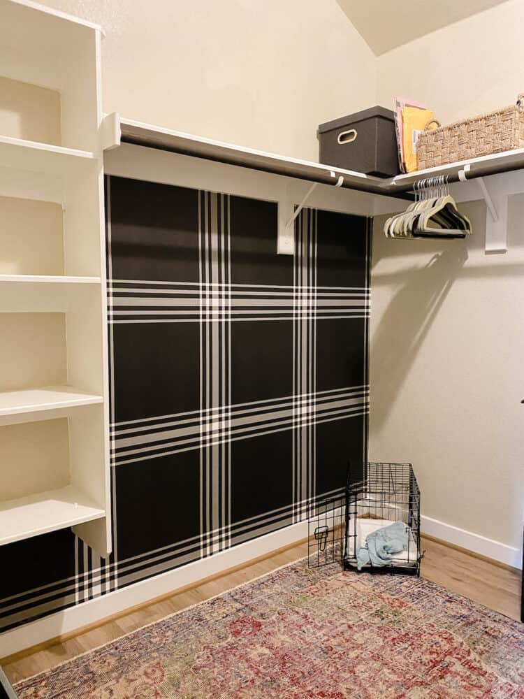 Closet with black plaid wallpaper and a vintage rug