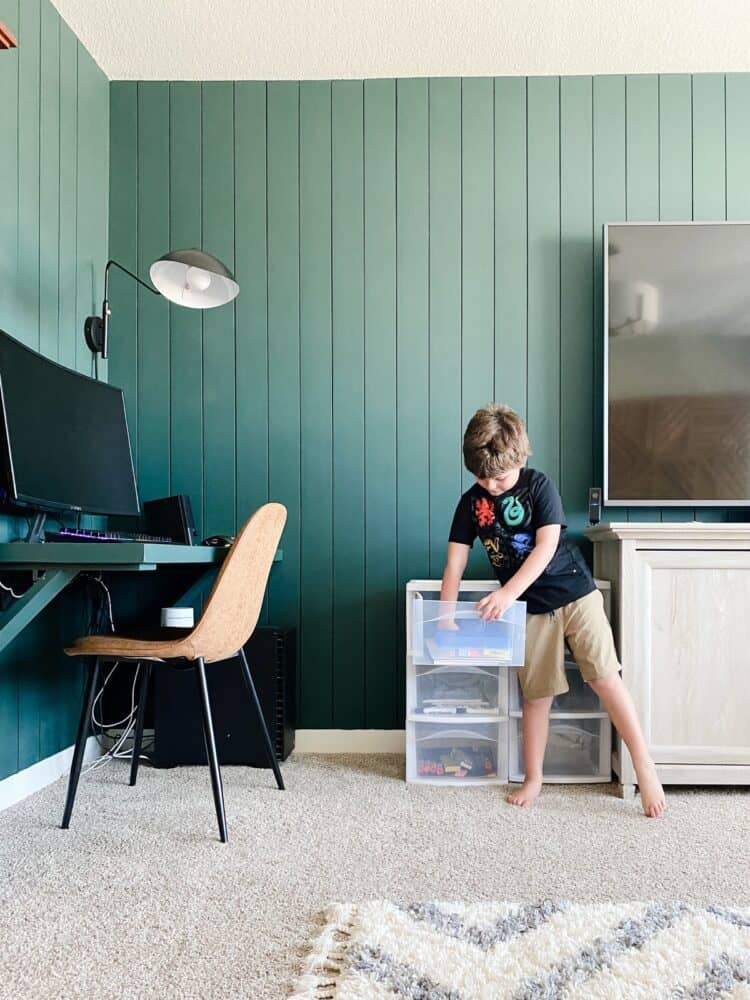 young boy grabbing school supplies from a set of plastic drawers