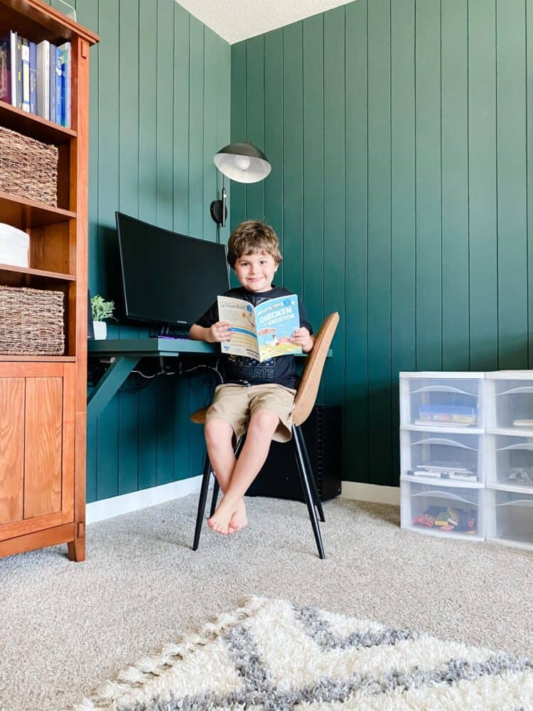 A young boy sitting at a corner work station with a book