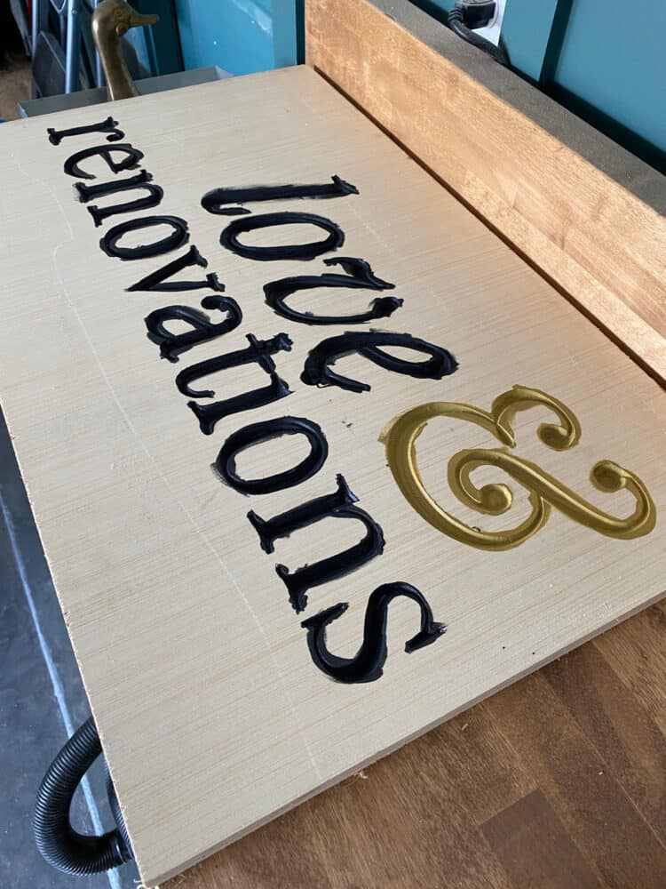 carved wood sign with letters painted