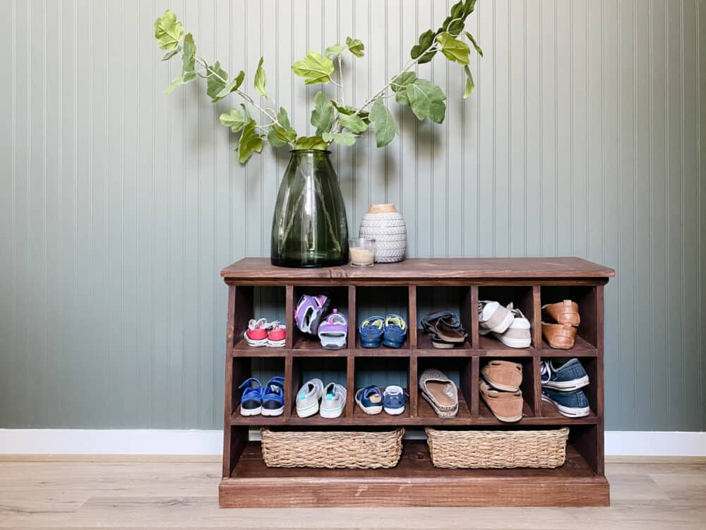 wooden shoe cubby in front of a dark green wall