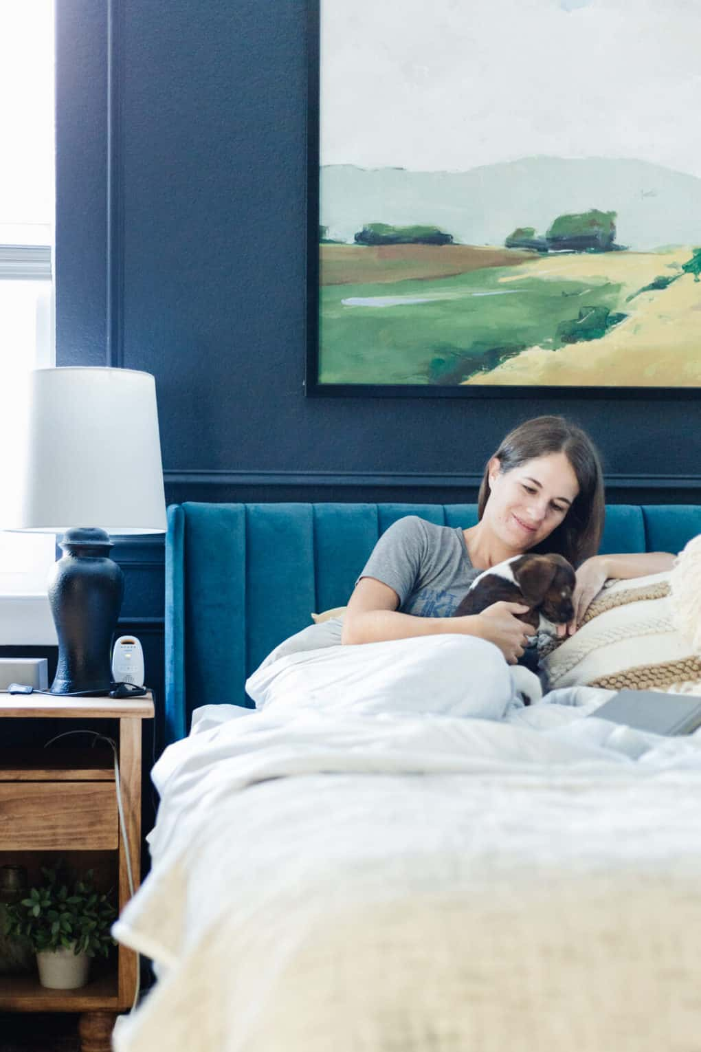 woman sitting on a bed using a weighted blanket and playing with a small puppy