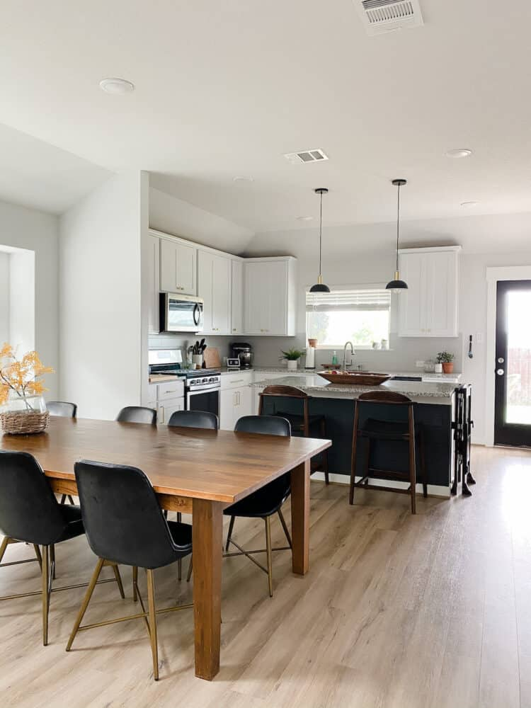 an open-concept living and dining room with a dark gray island