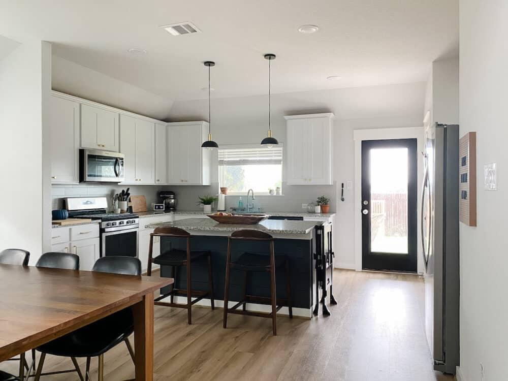 A white kitchen with a dark gray kitchen island