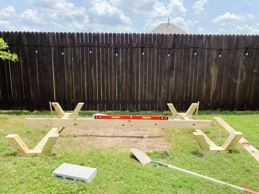 Supports for DIY playhouse laying in grass with a board and level between them