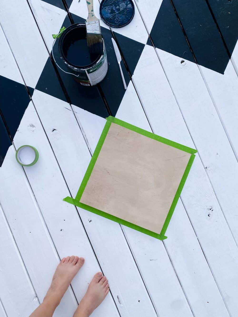 overhead view of painted decking with template for painting a diamond pattern
