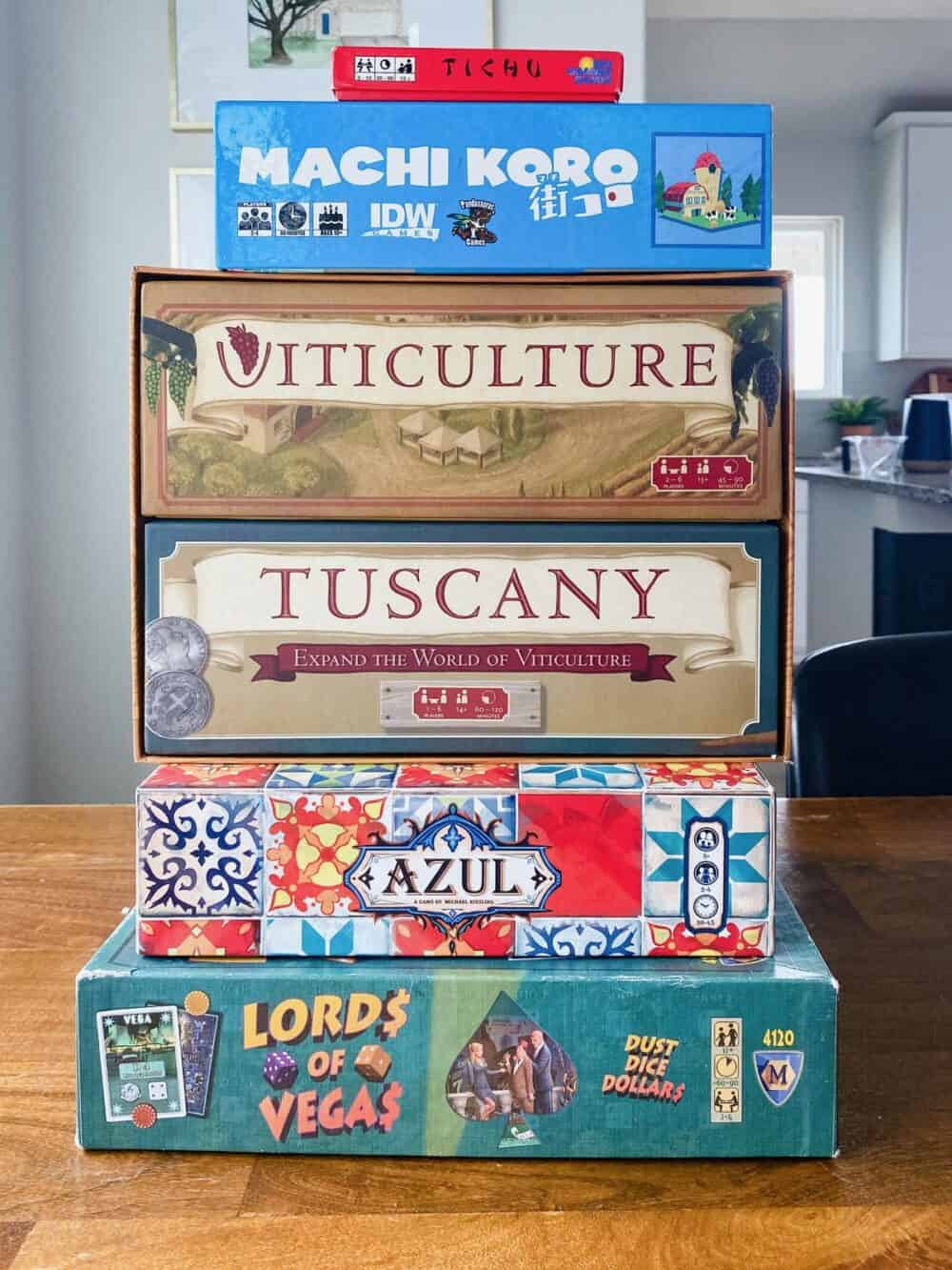 A stack of board games, including Tichu, Machi Koro, Viticulture, Azul, and Lords of Vegas