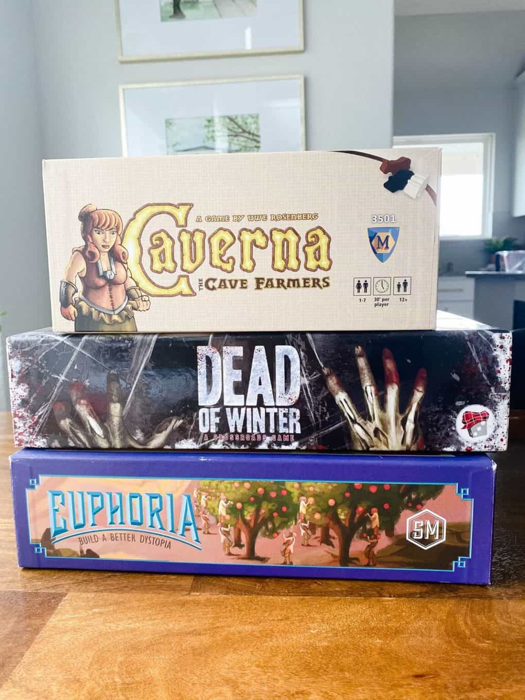 Stack of heavy board games, including Caverna, Dead of Winter, and Euphoria
