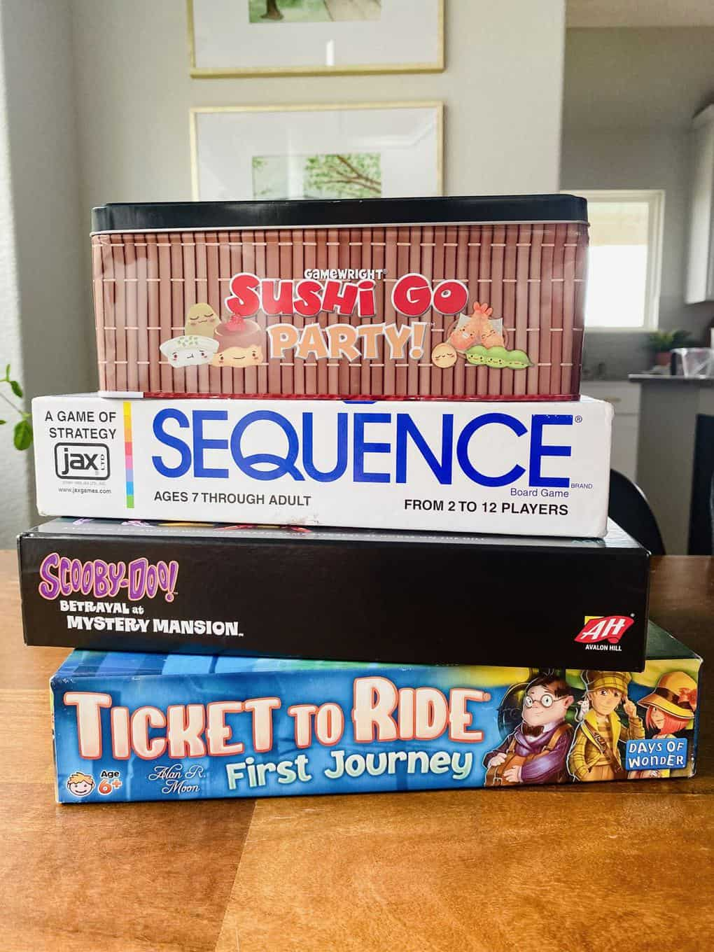 Stack of board games for kids, including Ticket to Ride First Journey, Betrayal at Mystery Mansion, Sequence, and Sushi Go